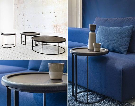 luxuriöses wohnzimmer interieur mit blauer akzentwand, modernem polstersofa in marineblau und designer holzcouchtischen rund