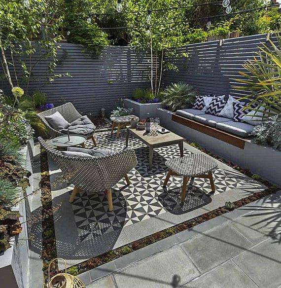 kreative gartensitzecke idee im grau mit gemauerter sitzbank mit hochbeeten, modernen Gartenmöbeln aus holz und rattan, holzsichtschutzmauer grau und cooler bodengestaltung mit mosaik und fettpflanzen