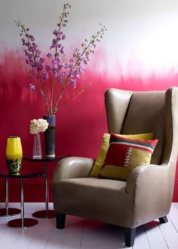 interieur design idee mit ombre wand in rosarot, weißem holzboden, ledersessel in beige und runden beistelltischen schwarz mit deko in gelb