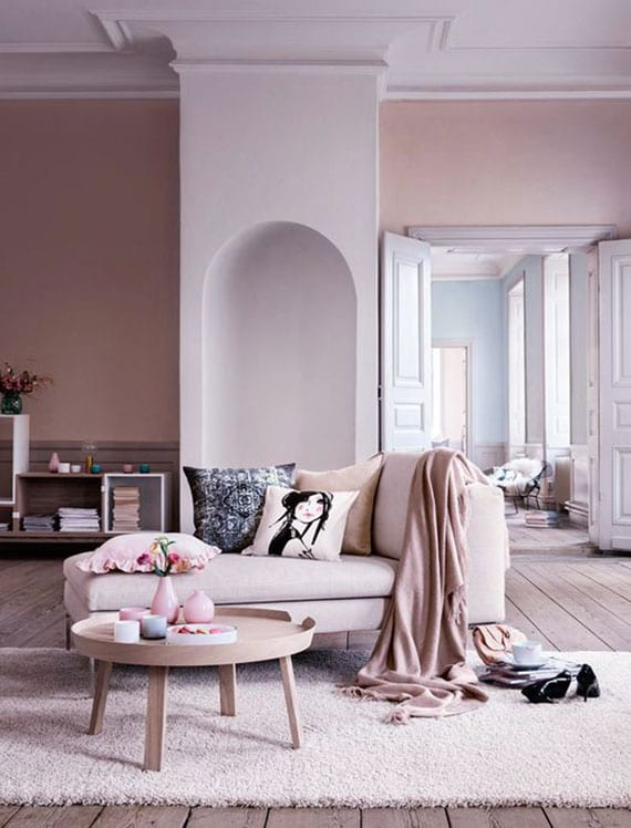 weibliche wohnzimmer gestalten mit wandfarben hellrosa und weiß, polsterliege mit gemusterten dekokissen und bettdecke in rosa, rundem couchtisch holz und creme teppich auf holzboden