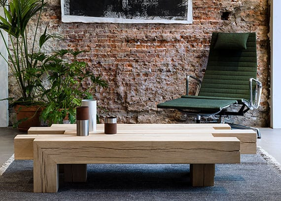 attraktive wohnzimmer gestaltung mit akzentwand aus ziegeln, elegantem schaukelstuhl grün und modernem kaffeetisch aus holzbalken