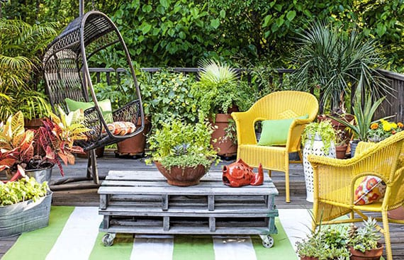 coole terrassengestaltung für holzterrasse mit teppich, diy palettentisch, rattanstühlen gelb,hängestuhl und pflanzen in terrakottatöpfen