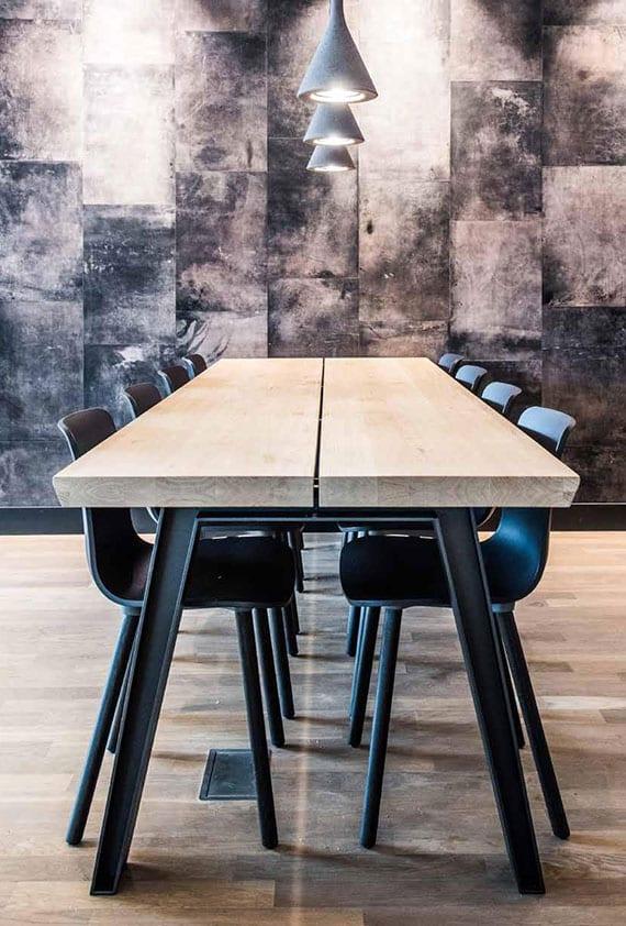 stilvolle Küche- und Esszimmereinrichtung mit ausgefallenem Massivholztisch, schwarzen Designerstühlen und modernen Pendellampen aus Beton