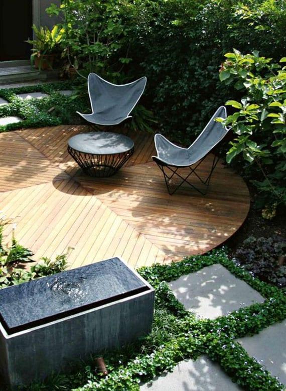 gemütlicher sitzbereich im kleinen garten mit rundem kaffeetisch und klappstühlen auf rundem holzpodest, trittsteinen mit grüner fugen und wasserspiel naturstein