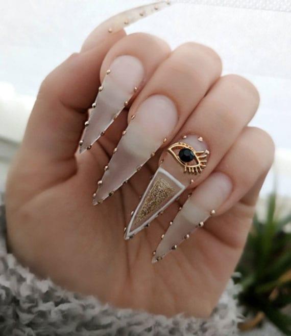 spitze nägel mit goldenen steinchen und egiptische motive als idee für moderne lange maniküre