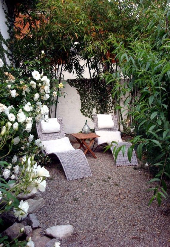 romantische gartengestaltung mit rattanliegen, holzklapptisch und weißem rosastrauch als verborgene sitzecke im kleinen garten mit kiesboden