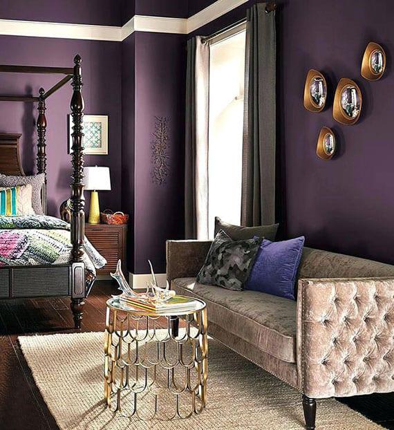 lila wandfarbe für glamouröse schlafzimmergestaltung mit himmelbett aus holz, sofa aus plusch in beige und rundem couchtisch gold auf teppich in creme und attraktive wanddeko mit rundem spiegeln in gildenen rahmen