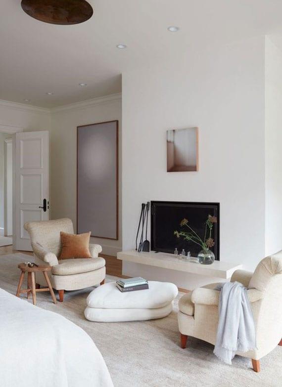coole schlafzimmer weiß mit kamin und gemütlicher sitzecke vor dem bett, sessel in creme mit polstercouchtisch weiß und holzhocker als beistelltisch auf teppich beige