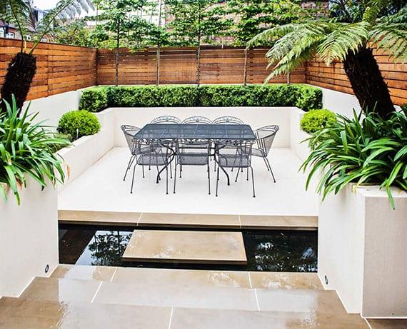 kleiner senkgarten mit essbereich modern gestalten mit wasser,gartensichtschutz aus holz, palmen und buchsbäumen in weißen gemauerten hochbeeten