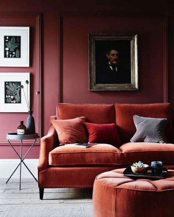 wohnzimmer attraktiv und stilvoll gestalten mit sofa und rundem hockertisch in fuchsfarbe, akzentwand mit bildern in rötlichem braun und grauem holzbodenbelag mit teppich
