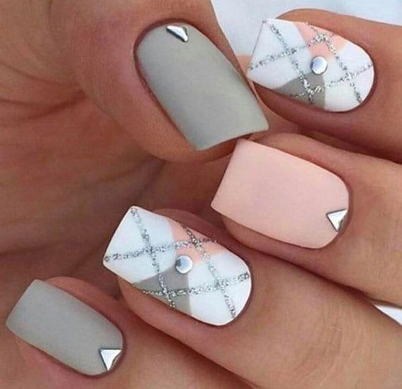 coole maniküre mit mattnagellack in grau, hellrosa und weiß, kleinen nagelsteinchen metall und brokat