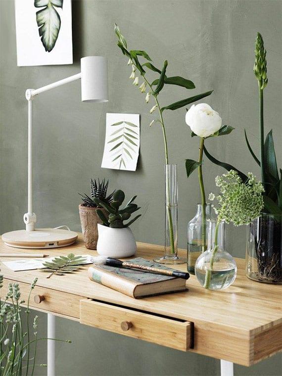 schickes interior design mit wandfarbe grün, weiße Tischlampe und Bürotisch aus hellem holz mit frischen blumen in glasvasen