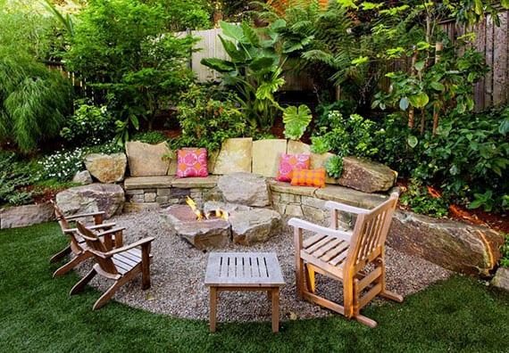 coole gartengestaltung ideen für sitzplatz mit feuerstelle aus steinen, holzgartenstühlen, bunte kissen und kiesboden