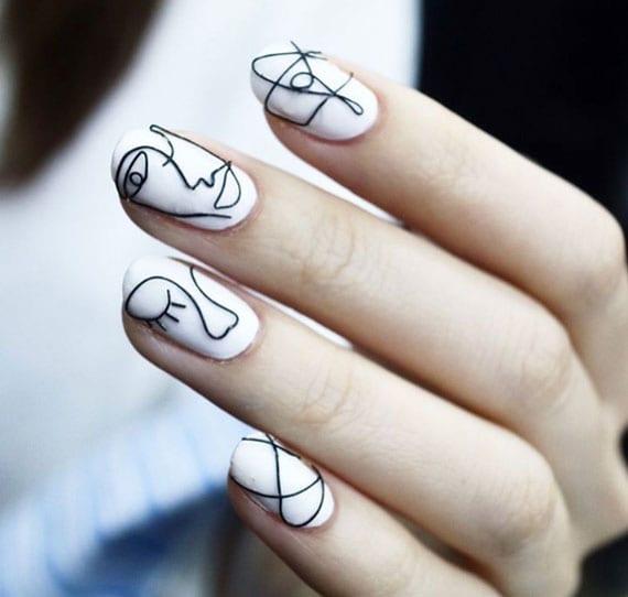 coole nagelkust mit weißem nagellack und schwarzem muster aus draht