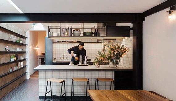 post modern interieur kleiner wohnk che mit k cheninsel barhocker und essgruppe aus holz. Black Bedroom Furniture Sets. Home Design Ideas