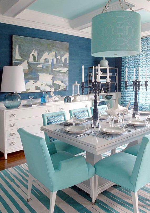 esszimmer interieur design im wohnstil maritim mit akzentwand in dunkelblau, hängelampe und esstischstühel in türkis, weißen sideboard und esstisch aus holz, teppich in weiß und türkis