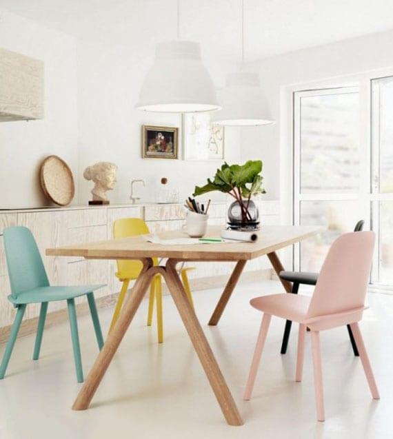 moderne küche in weiß mit hellem bodenbelag,holzküchenschränken,holzesstisch mit stühlen in pastellfarben und weißen pendellampen