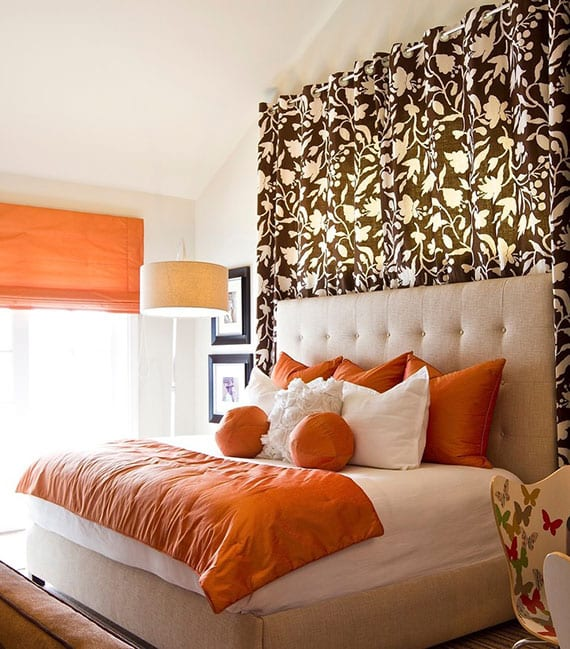 coole schlafzimmer farbgestaltung mit orangen kissen und fensterrollos, doppelbett mit kopfteil in beige, vorhang braun mit weißem blumenmuster und wandfarbe beige
