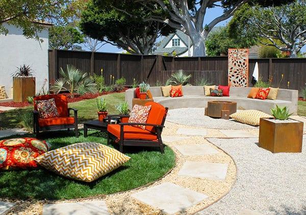 verschiedene sitzbereiche im garten definieren durch gartenwege und sitzflächen in kreisform, kiesgarten mit farbakzent orange, runde feuerstelle, gerundete sitzbank gemauert