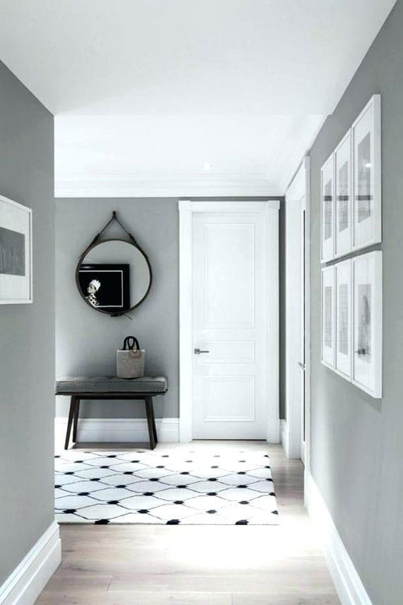 coole gestaltungsidee flur mit wandfarbe grau, holzboden, zimmertüren weiß, teppich in schwarz-weiß, holzsitzbank, rundem wandspiegel und wanddeko mit weißen bilderrahmen