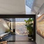 moderne kleine küche mit schiebetür zum hinterhof, sitzgruppe aus Eukalyptus-Holz, schwarze Akzente aus baustahl und natürliche beleuchtung durch schmales dachfenster