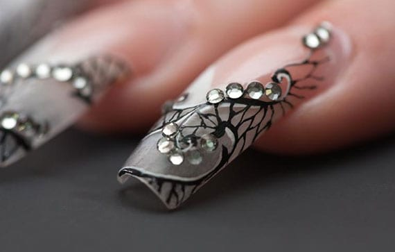 fingernageldesign mit spitzenmuster schwarz und strasssteinchen für lange maniküre