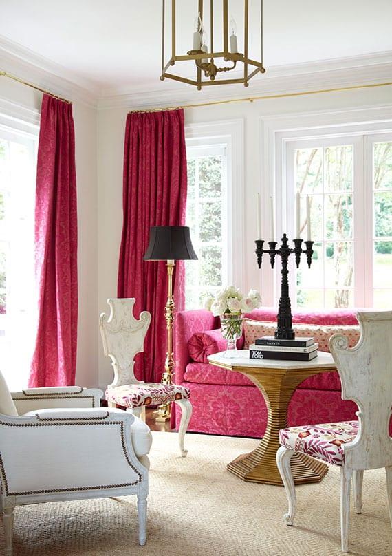 wohnzimmer interieur im klassischen stil mit gardinen und sofa in pink, holzstühen und ledersessel in weiß, rundem couchtisch und lampen in gold