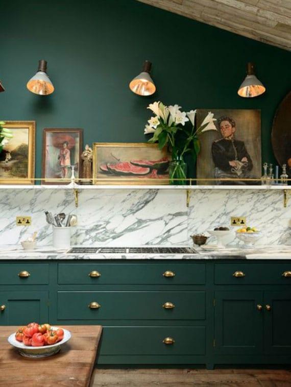 moderne küche im klassischen stil mit dachschräge, holzboden, holzesstisch, akzentwand in grün hinter küche mit marmor arbeitsplatte und spritzwand, küchenschränke grün und wandlampen über wandregal