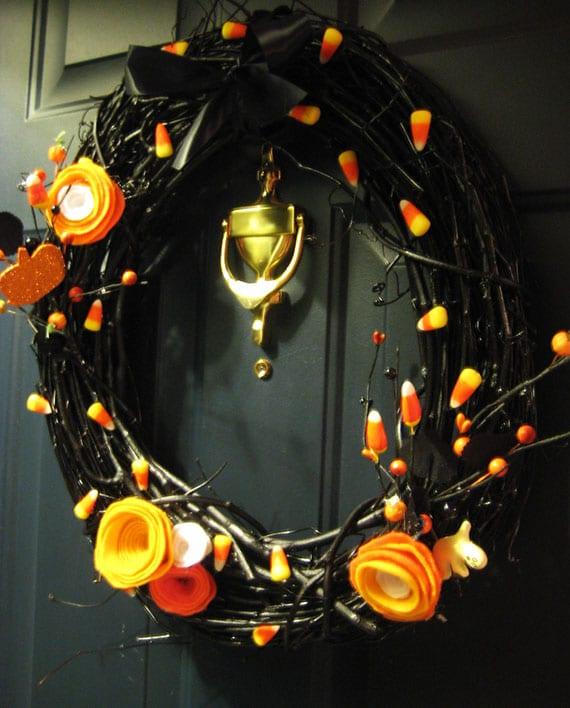 coole bastelidee für diy Türkranz zu halloween mit schwarzen zweigen, orangen filzblumen und Candy Corns