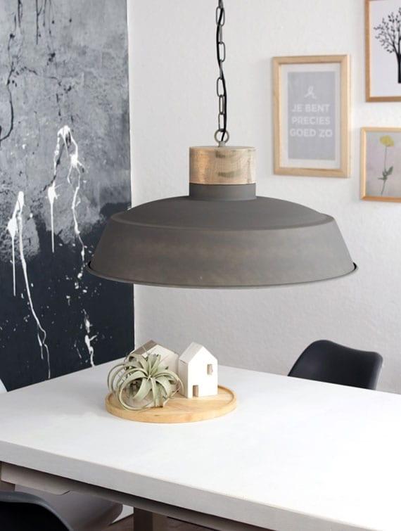 kleine küche mit modernem interieur in weiß und grau mit runder pendellampe aus metall, esstisch weiß, akzentwand grau und wanddeko mit holzbilderrahmen