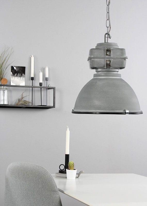 wohnküche mit essbereich modern gestalten in grau mit runder pendelleuchte metall, weißem esstisch mit grauen stühlen und wanddeko mit metallregal schwarz, glasvase und weißen kerzen