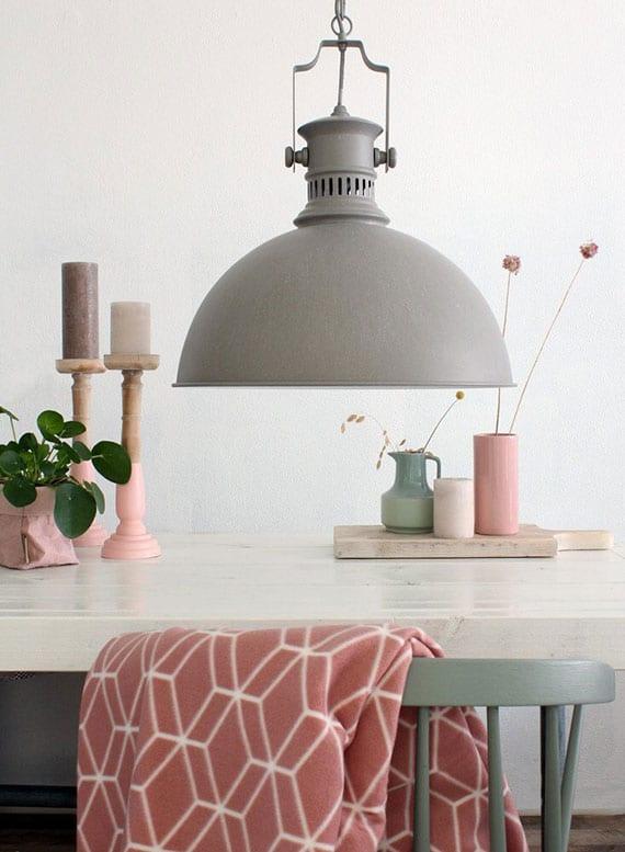 elegante küchengestaltung mit metall-hängelampe grau über esstisch weiß mit holzstühlen in pastellgrün und tischdeko mit vasen und kerzenhaltern in rosa