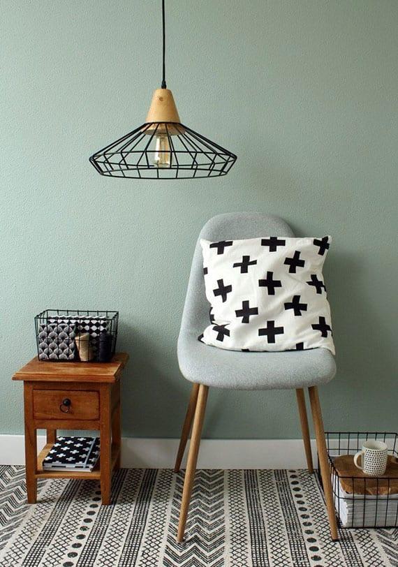 coole gestaltungsideen mit designer pendellampen aus metall und holz, gitterkörben, wandfarbe pastelgrün, beistelltisch holz und weißen textilien mit scharzem muster