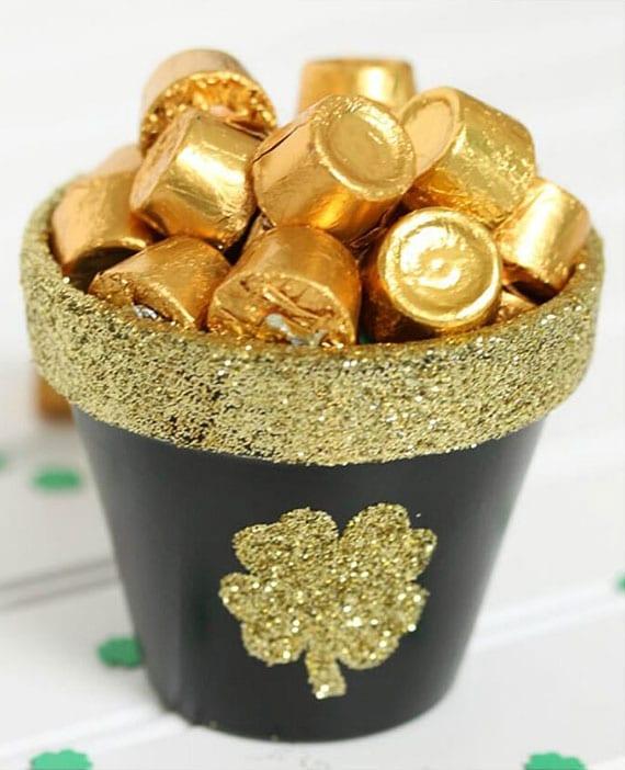 attraktive bastelidee für diy tischdekoration mit schoko bonbons in schwarzem blumentopf mit goldenen glitzern