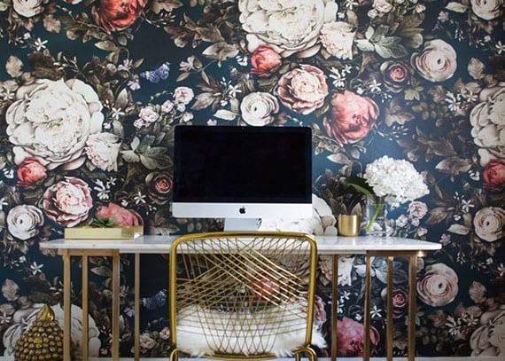 homeoffice im wohnzimmer einrichten mit schmalem metalttisch weiß, metallstuhl gold und wandtapete schwarz mit weißen und rosafarbigen blumen