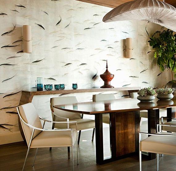 elegantes esszimmer interieur mit holzesstisch, lederstühlen in creme, sideboard holz, zylinder wandleuchten, wandtapete mit fischen und designer hängeleuchte