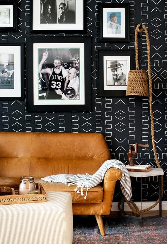 schwarze akzentwand im wohnzimmer tapezieren hinter ledersofa braun, beistelltisch marmor, wandleuchte aus rattan und hockertisch beige, wanddeko mit fotos in schwarzen bilderrahmen