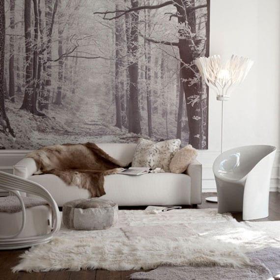 gemütliche wohzimmergestaltung mit winter fototapete wald, polstersofa weiß, pelzteppich weiß, kuhfell und designer stehlampe weiß