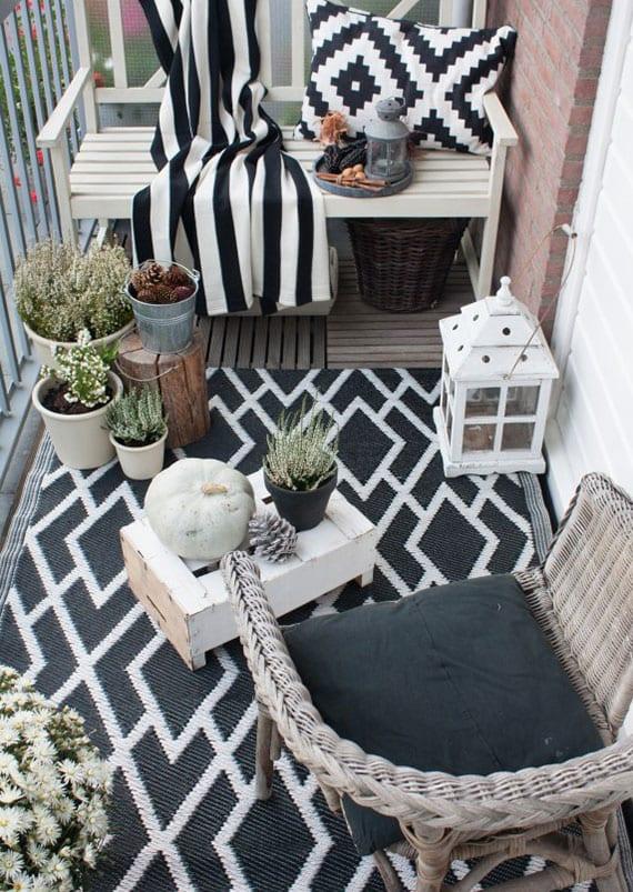 balkon im herbst schick gestalten mit teppich und decke in schwarz-weiß, weißen Herbstblumen und natürlicher deko mit zapfen, kürbis und holz