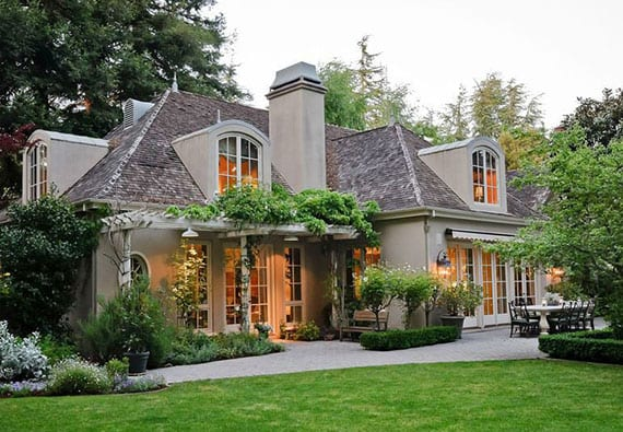 attraktives einfamilienhaus im landhausstil mit holzpergola weiß, gaubenfenstern und wunderschöne gartengestaltung mit kletterpflanze und sträuchern