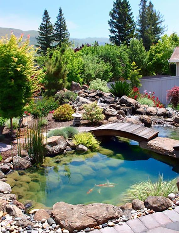 traumgarten gestalten mit kleinem Naturteich, Holzbrücke, Felsensteinen und passende Begrünung für Steingarten