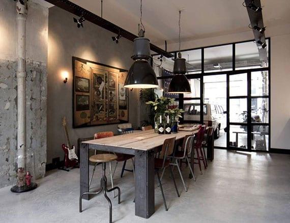industrielles Küche-Design mit Vintage-Essgruppe, schwarzen scheinwerfern als pendellampen, zementwänden und verglasung zur garage