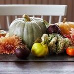 tisch hebstlich dekorieren mit Dahlie,Kakis,Artischocken,Quitte, Trauben und Zierkürbissen