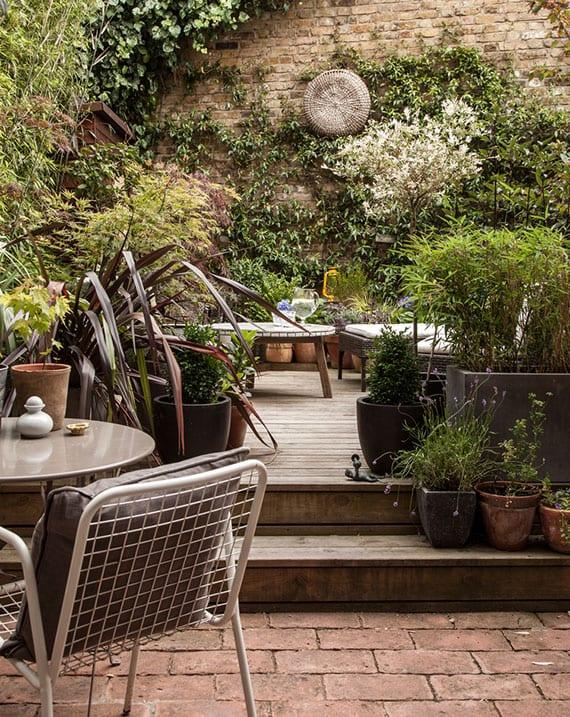 rustikale gartengestaltung mit terrassenboden aus ziegeln und holz, gemütlicher sitzecke mit rundem kaffeetisch und rattan stühlen, autentischer mauerdeko und begrünung mit kletterpflanzen
