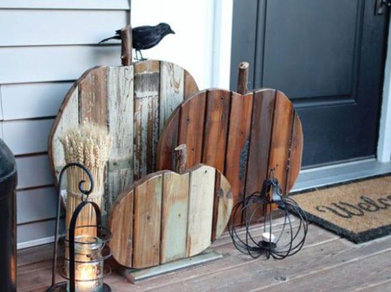 interessante herbstideen für außenbereich deko mit holz-kürbissen,scwarzen metall-laternen und bündel weizen
