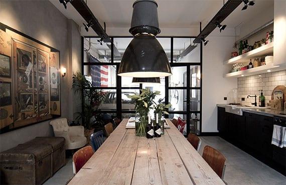 Vintage-Küche in schwarzweiß mit betonboden, grauer akzentwand, schwarzen leuchten, glastrennwand in schwarzen rahmen und holzesstisch mit rustikalen holzstühlen