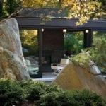 moderne gartengestaltung im aiatischen stil mit steingarten und schwarzen pavillion als gemütliche sitz- und unterchaltungsecke im garten