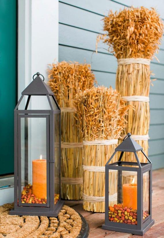 einfache herbstdeko eingangsbereich mit Bündeln-Hafe und orangen kerzen in schwarze laternen aus metall