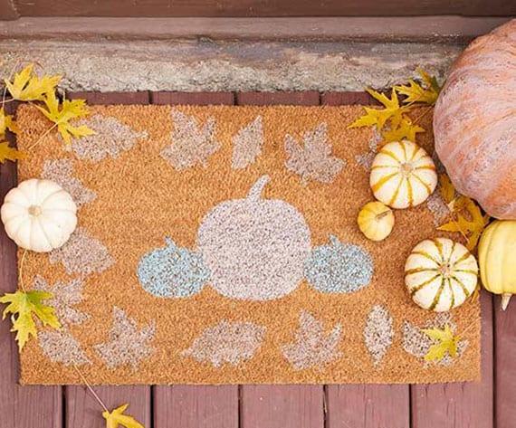 kreative herbstdeko eingangsbereich mit herbstlich gemusterter fußmatte, zierkprbissen und gelben herbstblättern