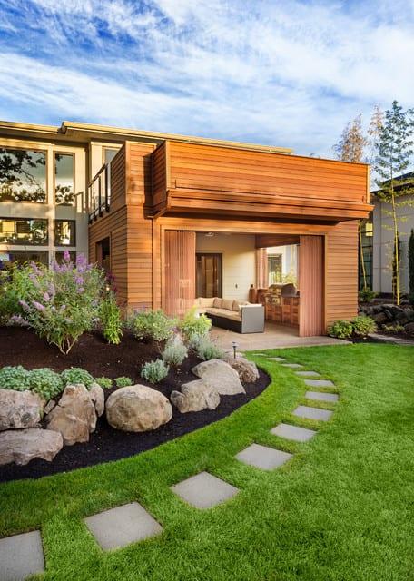 moderner garten mit überdachtem sitzbereich, rundem steingarten und wegführung mit rechteckigen steinplatten